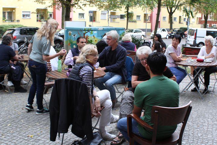 Viele Sprach-Café Teilnehmer/-innen, die sich auf der Terrasse des Nachbarschaftshaus aufhalten.