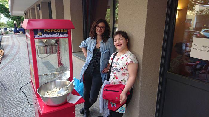 Neben einer roten Popcornmaschine steht ein Besucher-Kind mit einer Mitarbeiterin des Nachbarschaftshaus Friedenau.
