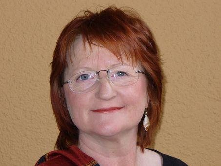 Die Kulturcafé-Mitarbeiterin Carmen Tillmann im Porträt, Frau mit Brille und längeren roten Haaren