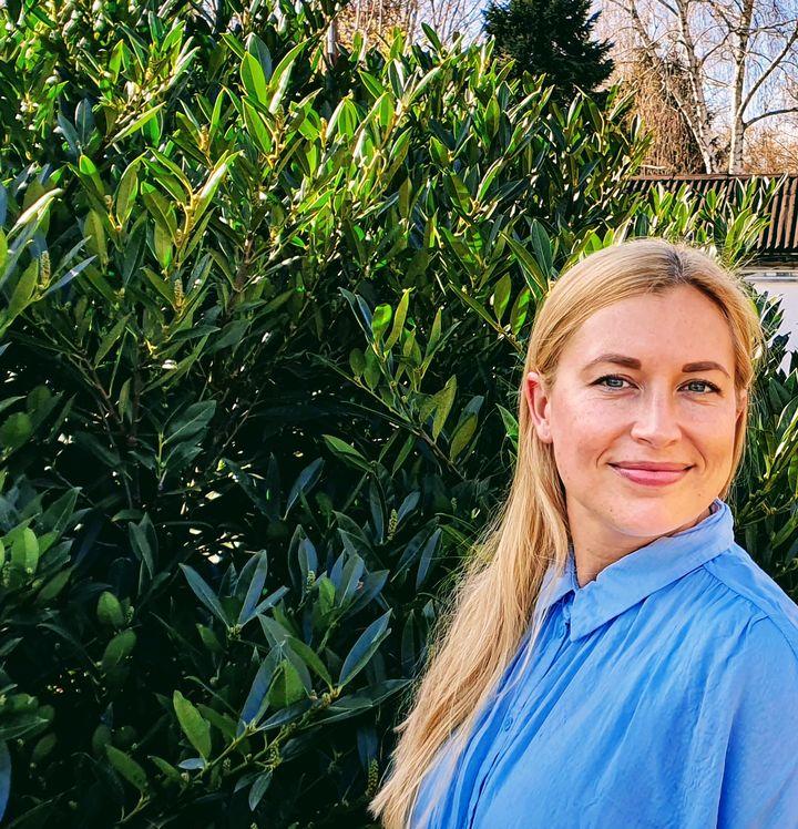 Portraitaufnahme von Romina Sabel, lächelnd und seitlich stehend vor einer grünen Hecke