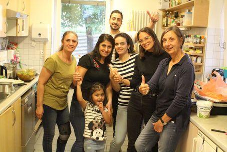 Mehrere Menschen unterschiedlicher Herkunft stehen zusammen in der Küche des Nachbarschaftscafé.
