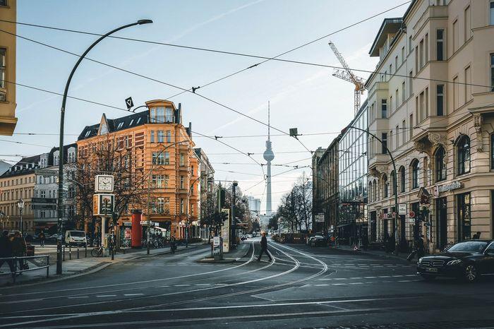 Eine Straßenkreuzung in Berlin Mitte, im Hintergrund ist der Fernsehturm zu sehen.