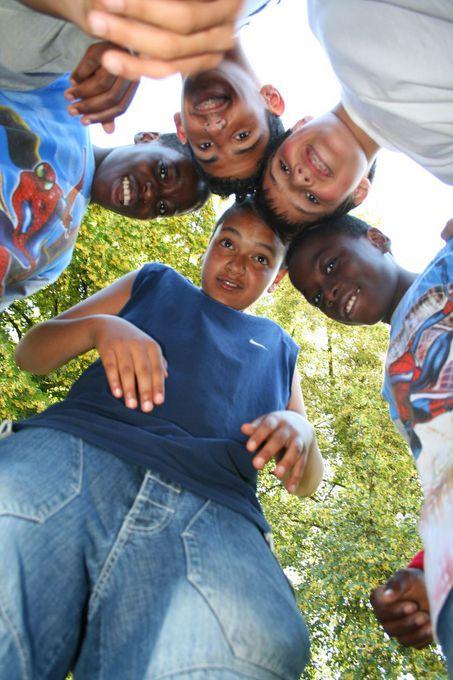 Kinder des Ferienprogramms lachen von oben in die Kamera.