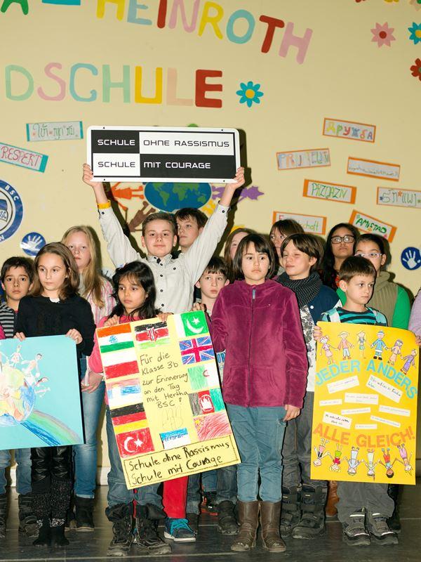 """Vierzehn Kinder stehen auf der Bühne in der Aula, drei halten stolz Plakate in der Hand zum Thema Anders sein sowie eines mit der Aufschrift """"Schule ohne Rassismus"""" in den Händen"""